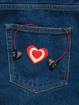 ブルージーンズのポケットの背景にヘッドフォンと赤と白のハート。ファッショナブルな服のロマンチックなスタイル。