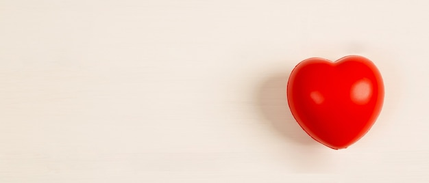 Наушники и красные сердца на белом деревянном фоне. уход за здоровьем и самолечение от болезней сердца