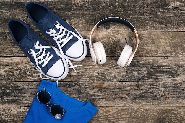 Наушники и кроссовки на деревянном деревенском столе. модные кроссовки, солнцезащитные очки и современные беспроводные наушники.