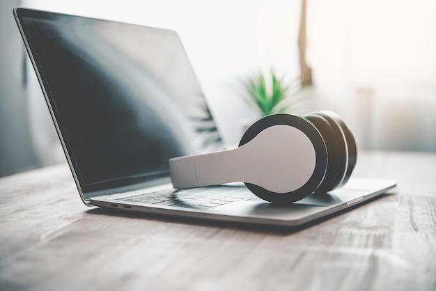 헤드폰은 노트북, 책상 위에 있습니다. . 휴식을 위한 음악의 개념