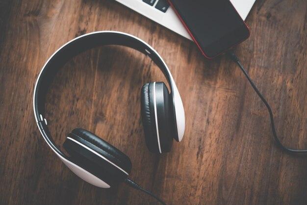 헤드폰은 노트북이 있는 책상 위에 있습니다. 휴식을 위한 음악 아이디어