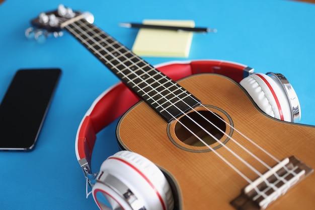 ヘッドフォンは青い背景のクローズアップにアコースティックギターを着ています