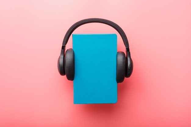 Headphones are worn on a book in a blue hardcover on a pink background, top view.