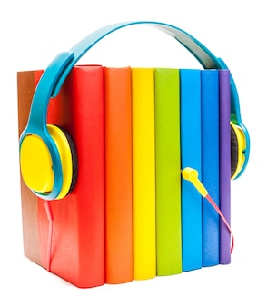 白いオーディオブックのコンセプトで分離された虹の多色本の周りのヘッドフォン