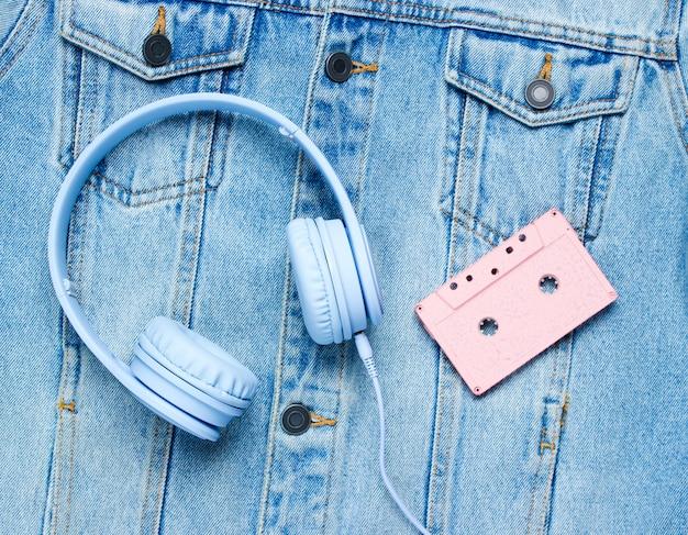 Headphones, audio cassette on denim background
