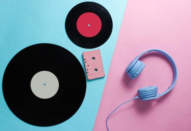 Headphones, audio cassette, lp records on pink blue background
