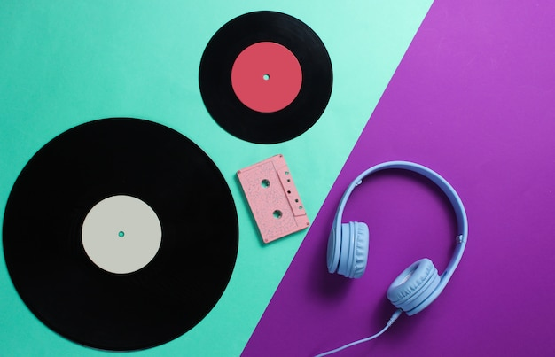 Headphones, audio cassette, lp records on purple blue background
