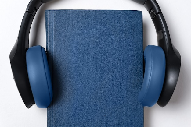 Headphones and blue book. audiobook concept.