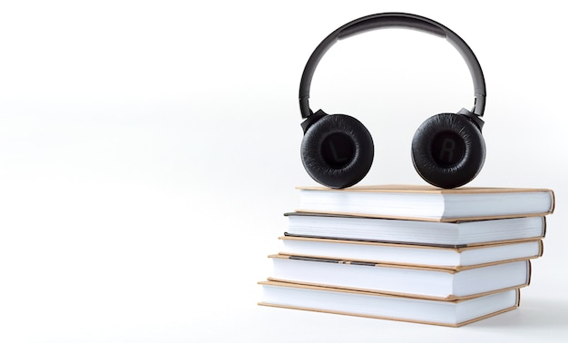 Headphones and books on a white background. audiobook concept with copy space.