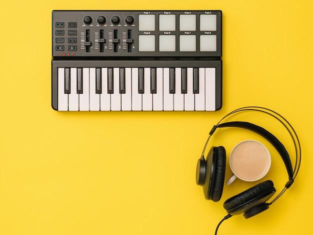 黄色の背景にヘッドフォン、コーヒー、音楽ミキサー。職場組織の概念。