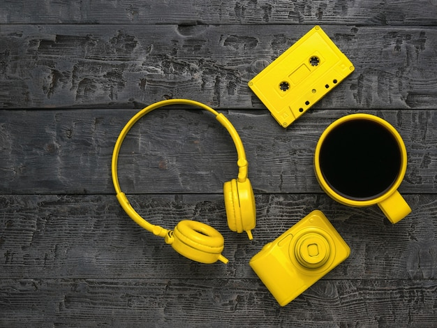 Headphones, coffee, a camera and a cassette on a wooden table. creative breakfast.