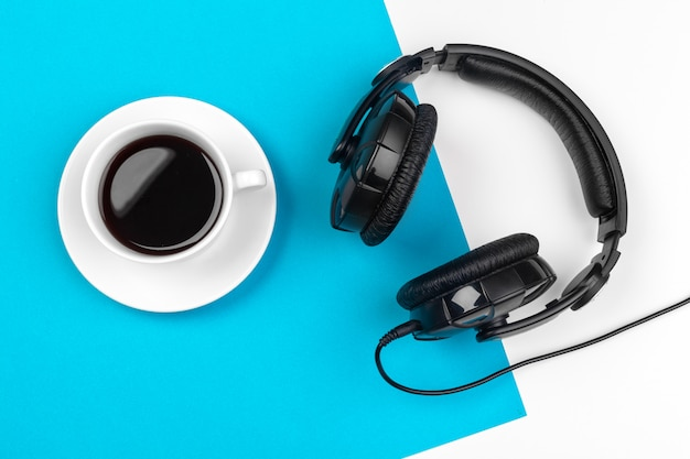Headphones and coffee cup on blue background, top view