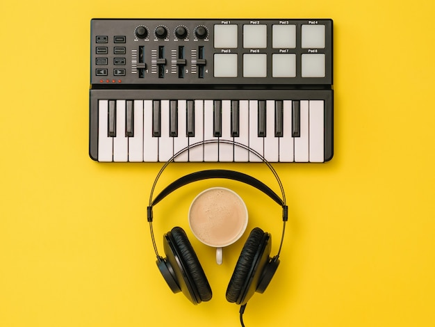 Headphones, coffee cup and music mixer on yellow background. the concept of workplace organization. equipment for recording, communication and listening to music.