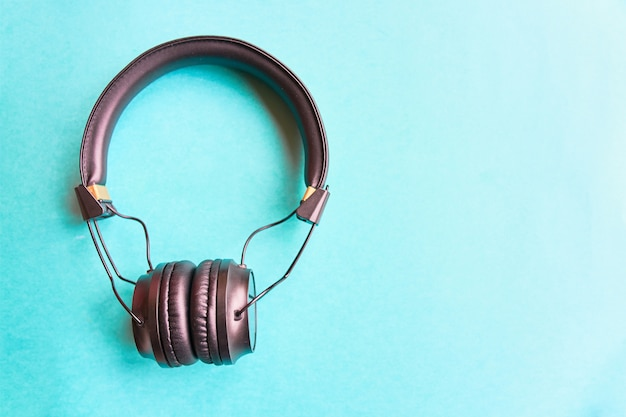 Headphones on colorful blue background. earphones for music sound on azure background.