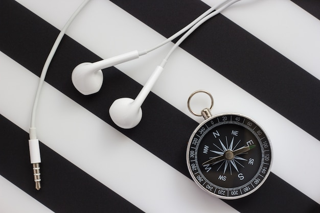 Headphones and compass on black and white background, close-up