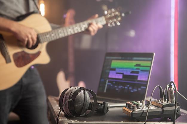 Наушники подключены к музыкальному микшеру и ноутбуку на музыкальной студии со студийным светом крупным планом.