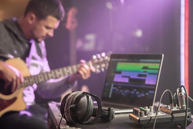 Наушники, подключенные к музыкальному микшеру и ноутбуку на музыкальной студии со студийным светом крупным планом.