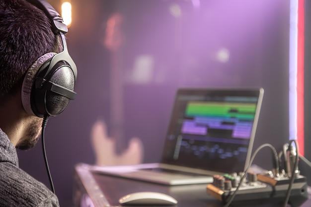 스튜디오 조명 음악 스튜디오의 음악 믹서 및 노트북에 연결된 헤드폰을 닫습니다.