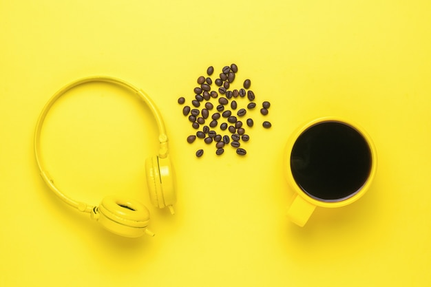 Headphones, a cup of coffee and coffee beans on a yellow background. morning accessories.