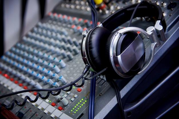Headphones on a dj control panel close-up.