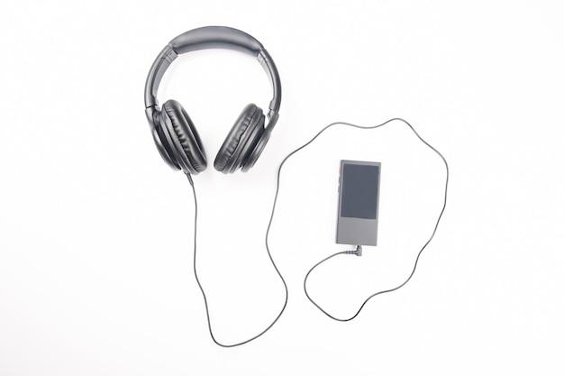 白い背景の上のデジタルオーディオプレーヤーで音楽を聴くためのヘッドフォン