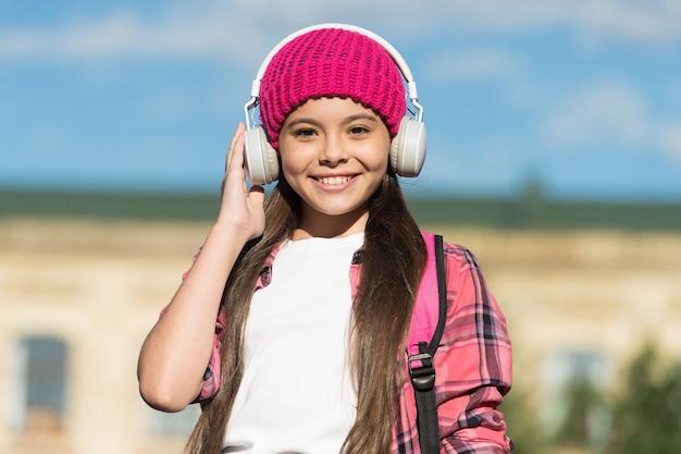 Наушники для безупречного звучания. счастливый ребенок слушать музыку в наушниках на открытом воздухе. веселье и развлечение. звуковые технологии. легкий и отлично подходит для маленьких ушей.