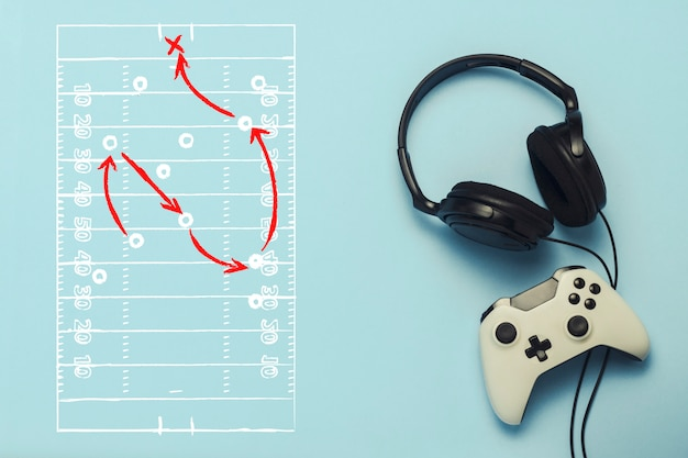 Headphones and gamepad on a blue background. added drawing with the tactics of the game. american football. the concept of computer games, entertainment, gaming, leisure. flat lay, top view.
