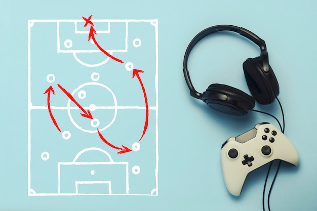 Headphones and gamepad on a blue background. added drawing with the tactics of the game. football. the concept of computer games, entertainment, gaming, leisure. flat lay, top view.