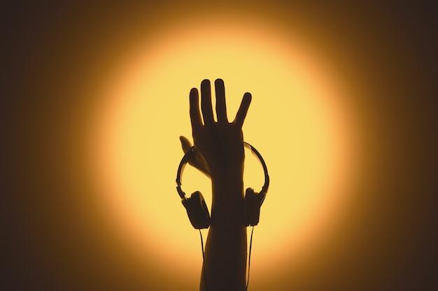 Наушники в руке. силуэт руки, поднятой вверх. музыкальная тема.