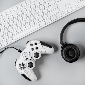 Наушники, джойстик и клавиатура на серой поверхности. концепция рабочего пространства геймера, вид сверху на игровое оборудование.