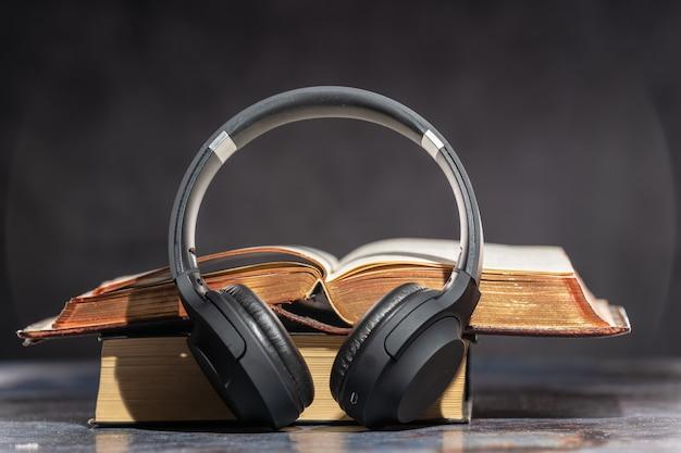 Наушники лежат рядом со старыми книгами. аудиокнига концепция.