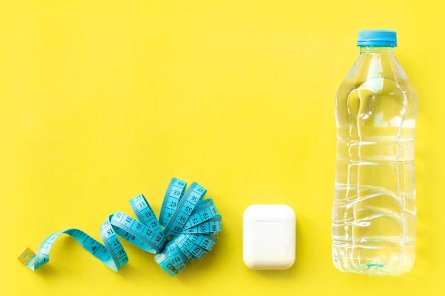 ヘッドフォン、メジャーテープ、黄色の背景に水のボトル。フィットネス、スポーツタイム、フラットレイ