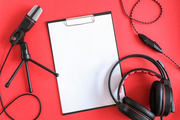 ヘッドフォン、マイク、赤の背景に白い紙でクリップボード。コンセプトミュージックまたはポッドキャスト。トップビュー、フラットレイアウト