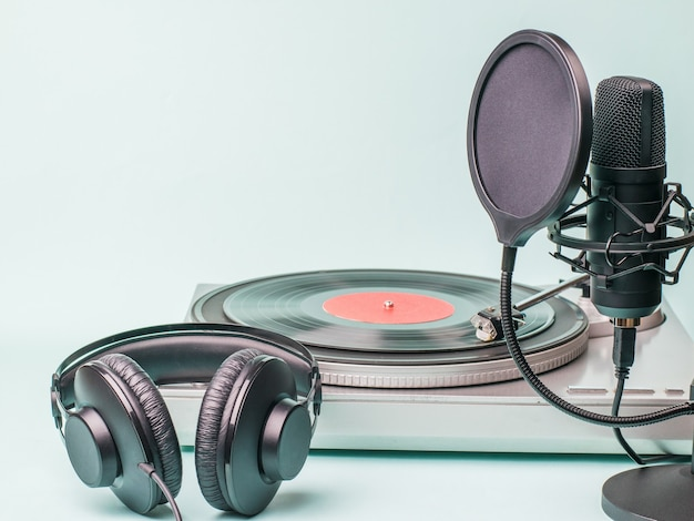 Headphones, microphone and vinyl record player on a light surface