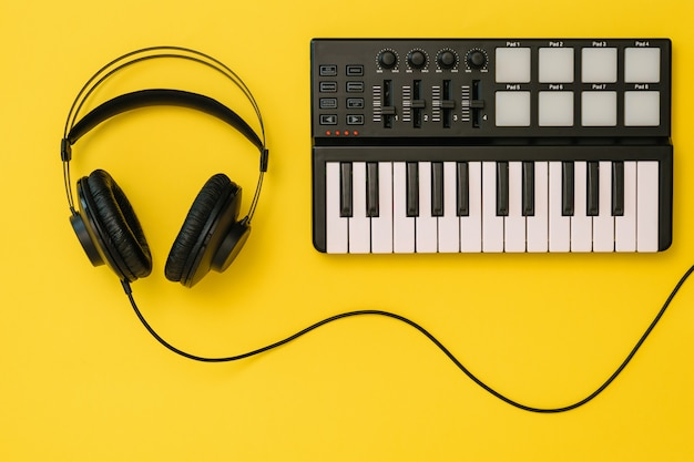 Headphones and music mixer on bright yellow