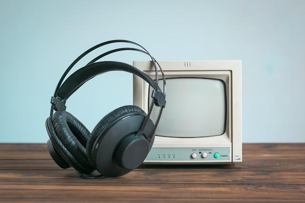 파란색 배경에 나무 테이블에 작은 오래 된 모니터 근처 헤드폰. 사운드 및 비디오 재생 기술.