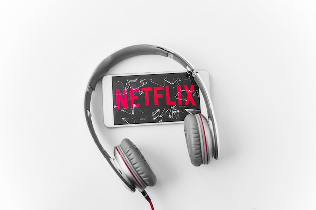 Headphones near broken smartphone with netflix logo