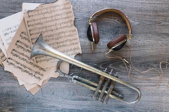Headphones near trumpet and sheet music