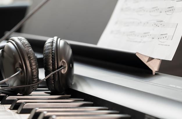 Наушники на музыкальной синтезаторной клавиатуре. наушники на электронном пианино. музыкальный фон