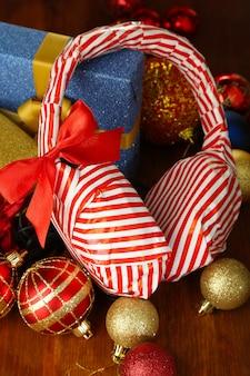 Наушники упакованы в подарочную бумагу с подарками на деревянном столе крупным планом