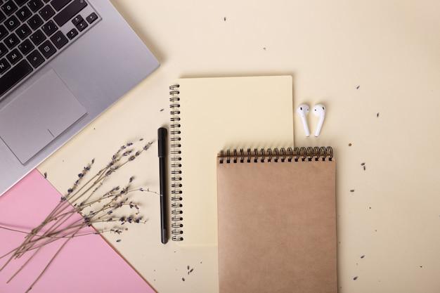 Наушники перьевые тетради и ветки лаванды красиво разложены рядом с ноутбуком ...