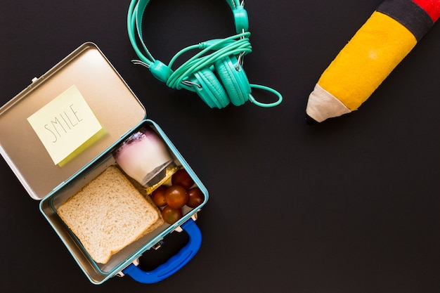 Headphones and pencil case near lunchbox