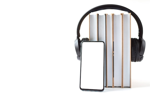 Headphones, phone and books on a white background. audiobook concept.