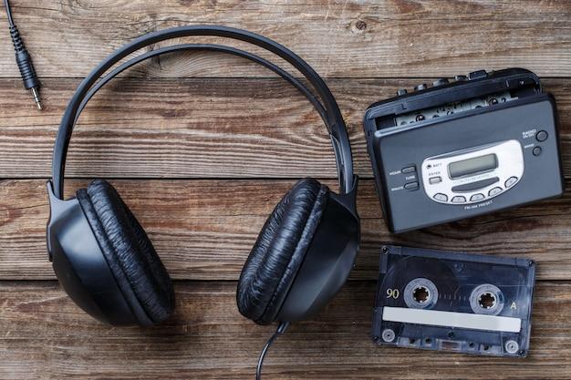 Наушники, плеер и ретро компактная кассета на деревянном фоне. вид сверху.