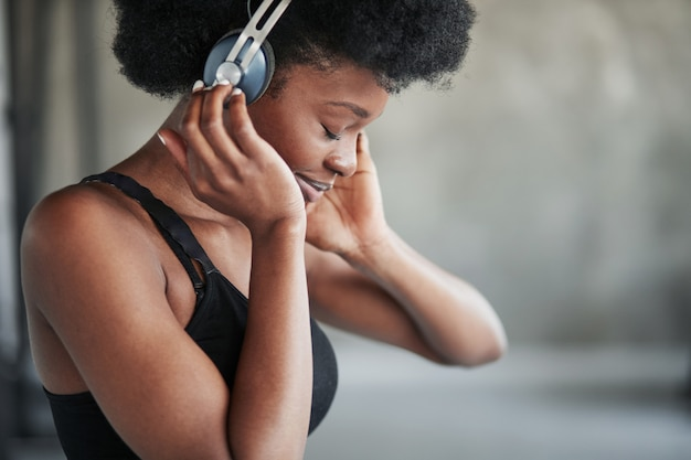 In headphones. portrait of african american girl in fitness clothes having a break after workout