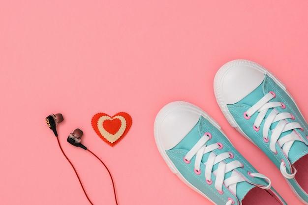 ヘッドフォン、赤と白のハート、ピンクの背景にターコイズブルーのスニーカー。 。スポーツスタイル。フラットレイ。上からの眺め。