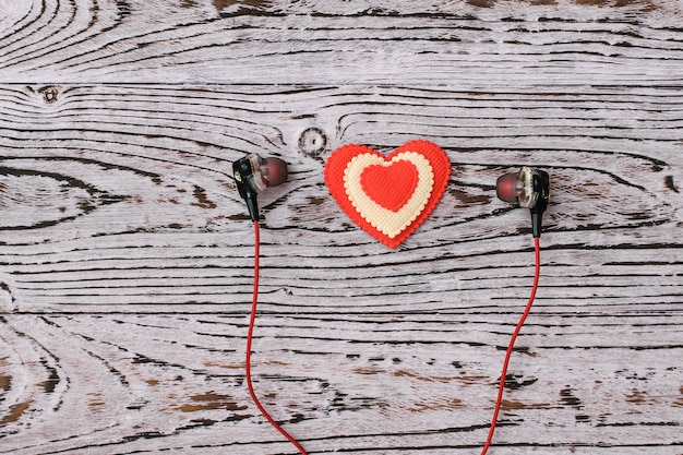 Headphones and red and white heart on a pink wooden