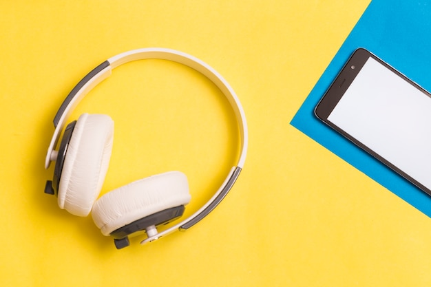 Headphones and smartphone on colorful background