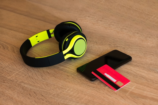 Headphones, smartphone and credit card on a table