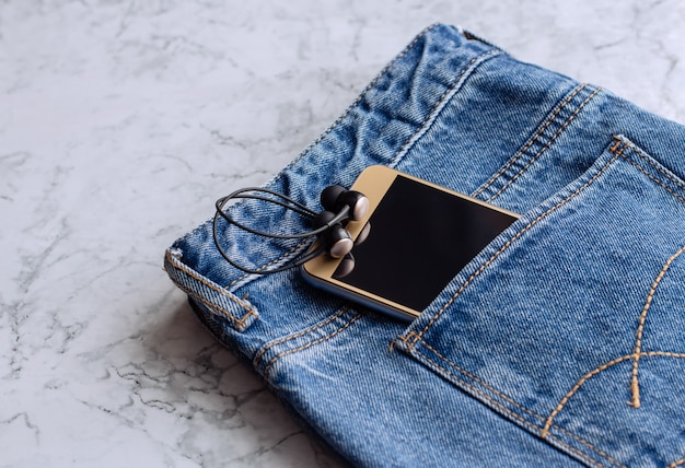 Headphones and smartphone in the pocket of jeans, close-up